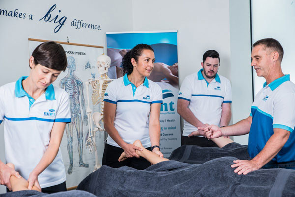 four students learning how to become a massage therapist