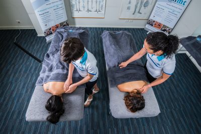 Two massage therapists practicing massage therapy