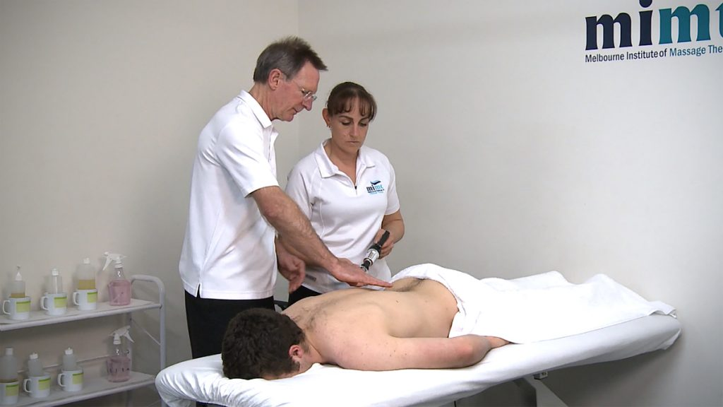 massage trainer teaching remedial massage to student