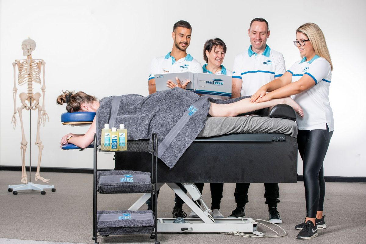 students with person lying on massage table